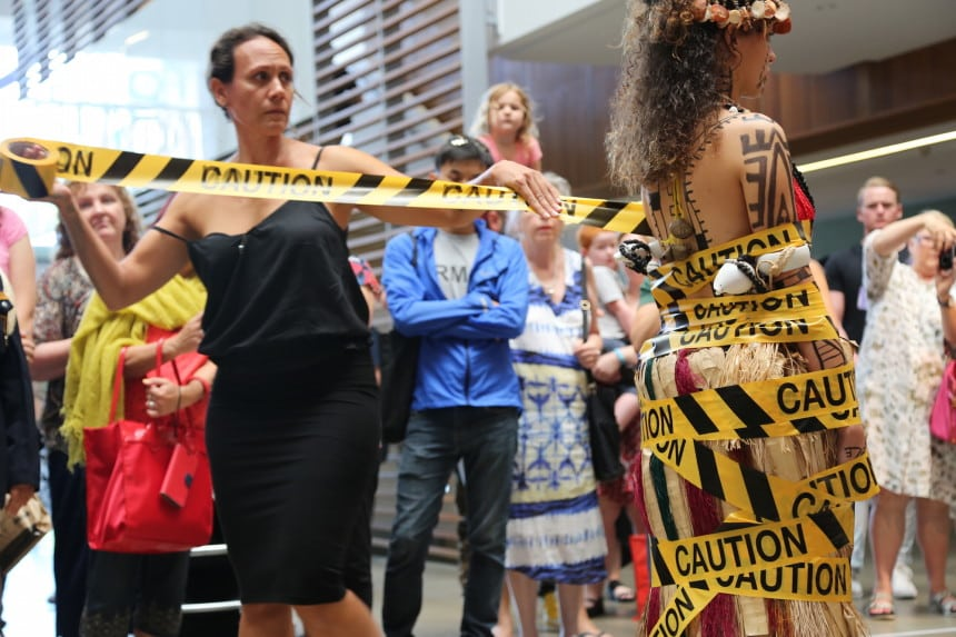 "Julia Mageau-Gray wrapping ""traditional, Papuan culture"" in caution tape to signify the labels that are placed on our culture."